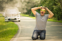 Desperate guy kneeing on the road because his car is broken Royalty Free Stock Photography
