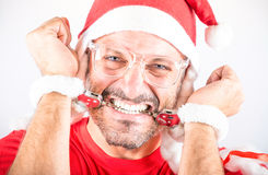 Desperate Handcuffed Santa Man. Portrait of a desperate man with Santa hat Royalty Free Stock Image