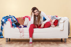 Desperate helpless woman in messy room home. Desperate helpless woman sitting on sofa couch in messy living room with hand on head. Young girl surrounded by Stock Photos