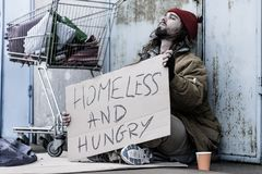 Desperate homeless and hungry tramp. With a sign sitting on the street next to a trolley and begging for food and money Stock Image