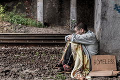 Desperate homeless woman. Poor homeless woman with sign sitting on the street near the rail track Royalty Free Stock Photos