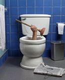Desperate house toillet. Hand reaches up through the seat from out of a toilet in a domestic bathroom stock image