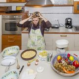 Desperate housewife with hands in the hair for mess in kitchen she will have to fix royalty free stock photo