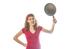 Desperate housewife threatening with a frying pan. Freaked out and enraged retro vintage housewife in red holding a frying pan, ready to punch someone Stock Image