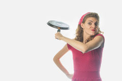 Desperate housewife threatening with a frying pan. Freaked out and enraged retro vintage housewife in red holding a frying pan, ready to punch someone Royalty Free Stock Image