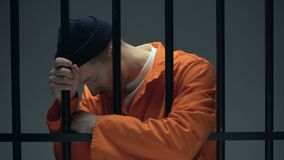 Desperate imprisoned male leaning on bars, feeling depressed, psychological help. Stock footage stock video