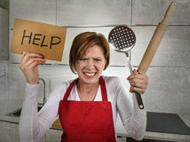 Desperate inexperienced home cook woman crying in stress desperate holding rolling pin and help sign Stock Photography