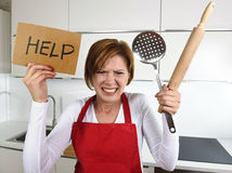Desperate inexperienced home cook woman crying in stress desperate holding rolling pin and help sign Royalty Free Stock Image