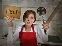 Desperate inexperienced home cook woman crying in stress desperate holding rolling pin and help sign. Young desperate inexperienced home cook woman crying in Royalty Free Stock Photography