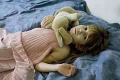 Desperate little girl lying on the bed Royalty Free Stock Photos