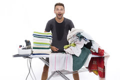 Desperate man behind an ironing board Royalty Free Stock Images