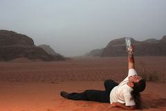 Desperate man in the desert drinking last drops of water from an empty bottle Stock Image