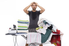 Desperate man with hands in his hair behind an ironing board Stock Photos