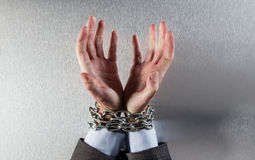 Desperate man hands tied with chain begging for employee victim. Desperate professional man hands tied with chain begging at the office for concept of employee Royalty Free Stock Photos