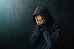 Desperate man in hooded jacket is crying. Hands are covering face and tears in the eyes, light of hope shining from his right side Stock Images