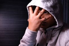 Desperate man in hooded jacket, hands are covering face and tears in the eyes.  Royalty Free Stock Photos
