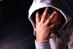 Desperate man in hooded jacket, hands are covering face and tears in the eyes.  Royalty Free Stock Photo