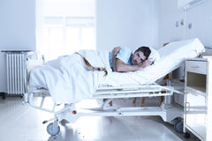 Desperate man at hospital bed alone sad and devastated suffering depression _. Young desperate man lying at hospital bed alone sad and devastated suffering stock photo