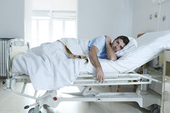 Desperate man at hospital bed alone sad and devastated suffering depression _. Young desperate man sitting at hospital bed alone sad and devastated suffering Royalty Free Stock Photos