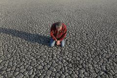 Farmer and drought in field. Desperate man kneeling and praying at dry cracked land after drought, natural disaster Royalty Free Stock Photo