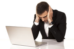 Desperate man on laptop. Desperate young businessman leaning on both hands behind his laptop Royalty Free Stock Photo