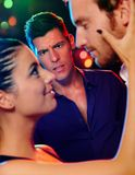 Desperate man looking at flirting couple in disco. Desperate jealous men looking at flirting couple in discotheque Royalty Free Stock Images