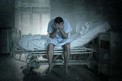 Desperate man sitting at hospital bed alone sad and devastated suffering depression crying at clinic. Young desperate man sitting at hospital bed alone sad and royalty free stock image