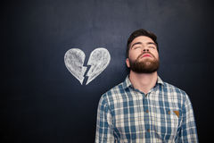 Desperate man standing over blackboard background with drawn broken heart. Portrait of unhappy desperate young man standing with eyes closed over blackboard Royalty Free Stock Image
