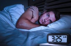 Desperate man in stress sleepless on bed with eyes wide opened suffering insomnia sleeping disorder depressed with digital alarm. Worried sad young attractive stock photo