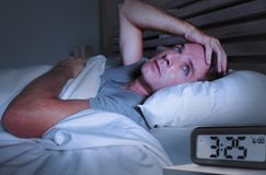 Desperate man in stress sleepless on bed with eyes wide opened suffering insomnia sleeping disorder depressed with digital alarm. Worried sad young attractive stock photos
