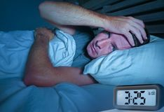 Desperate man in stress sleepless on bed with eyes wide opened suffering insomnia sleeping disorder depressed with digital alarm. Worried sad young attractive stock image