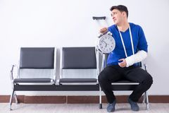 Desperate man waiting for his appointment in hospital with broke. N arm Stock Photo