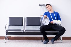 Desperate man waiting for his appointment in hospital with broke. N arm Royalty Free Stock Image