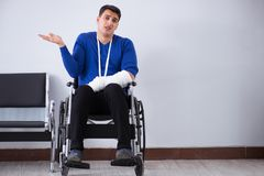 Desperate man waiting for his appointment in hospital with broke. N arm Royalty Free Stock Photo