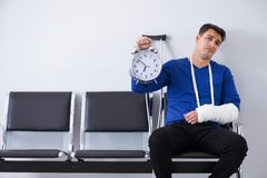 Desperate man waiting for his appointment in hospital with broke. N arm Stock Photography