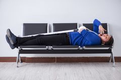 Desperate man waiting for his appointment in hospital with broke. N arm Stock Image