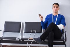 Desperate man waiting for his appointment in hospital with broke. N arm Royalty Free Stock Images