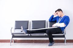 Desperate man waiting for his appointment in hospital with broke. N arm Stock Photos