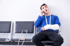 Desperate man waiting for his appointment in hospital with broke. N arm stock images