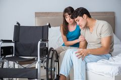 The desperate man on wheelchair with his sad wife. Desperate men on wheelchair with his sad wife Stock Photo