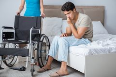 The desperate man on wheelchair with his sad wife. Desperate men on wheelchair with his sad wife Royalty Free Stock Photography