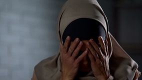 Desperate muslim woman crying, covering face with hands, family problem, shame. Stock photo stock photo