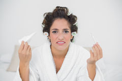 Desperate natural brunette holding thermometer and tissue Stock Photography