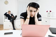 Desperate overworked woman working at desk and elegant man waiting in the background royalty free stock photo