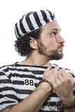 Desperate, portrait of a man prisoner in prison garb, over white Stock Photography