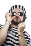 Desperate, portrait of a man prisoner in prison garb, over white Royalty Free Stock Photo