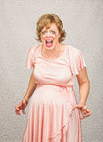 Desperate Pregnant Lady. Desperate pregnant person in pink dress on gray background Royalty Free Stock Images