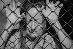 Desperate sad unhappy woman behind fence. Filtered image Portrait of devastated, stressed mature woman with closed eyes and hands gripped on behind mesh wire royalty free stock photography