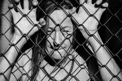 Desperate sad unhappy woman behind fence. Filtered image Portrait of devastated, stressed mature woman with closed eyes and hands gripped on behind mesh wire royalty free stock image