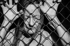 Desperate sad unhappy woman behind fence. Filtered image Portrait of devastated, stressed mature woman with closed eyes and hands gripped on behind mesh wire royalty free stock photo